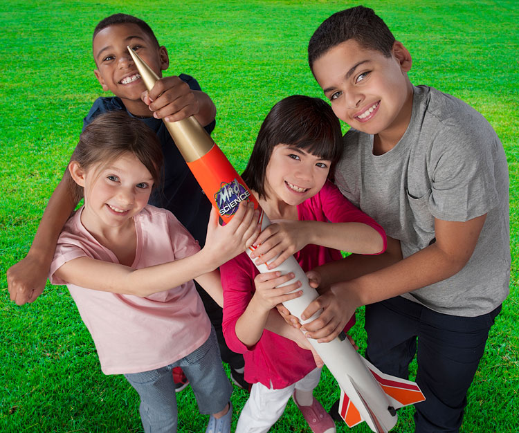 2 boys and 2 girls all holding a toy orange and white rocket with a mad science logo on it.