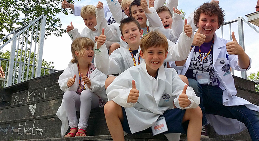 Kids wearing mad science lab coats sitting outside with a mad scientist with their thumbs up