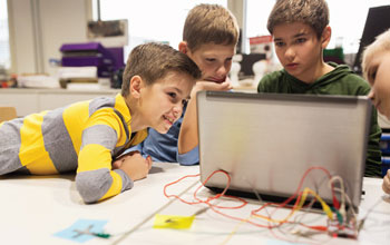 4 children looking at a computer with multicolored wires plugged in to a panel behind the computer.