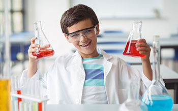 A boy in a white lab coat holding 2 flasks full of red liquid.